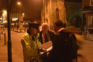 Sir Graham Bright watches PCSO Philip Hepworth provide safety advice to a Cambridge cyclist