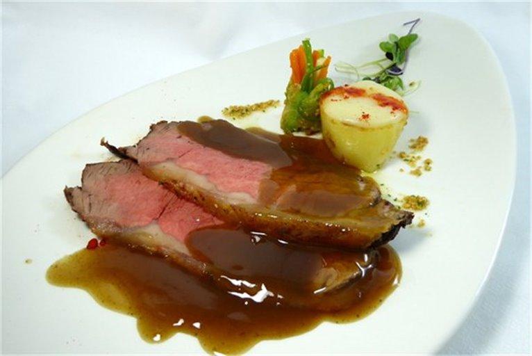 Roastbeef de presa de cerdo con salsa cumberland y patatas parisienne