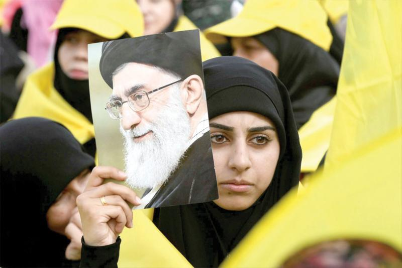 A Hezbollah supporter carries a picture of Iranian Supreme Leader Ayatollah Ali Khamenei during a rally in the Bekaa Valley, last May