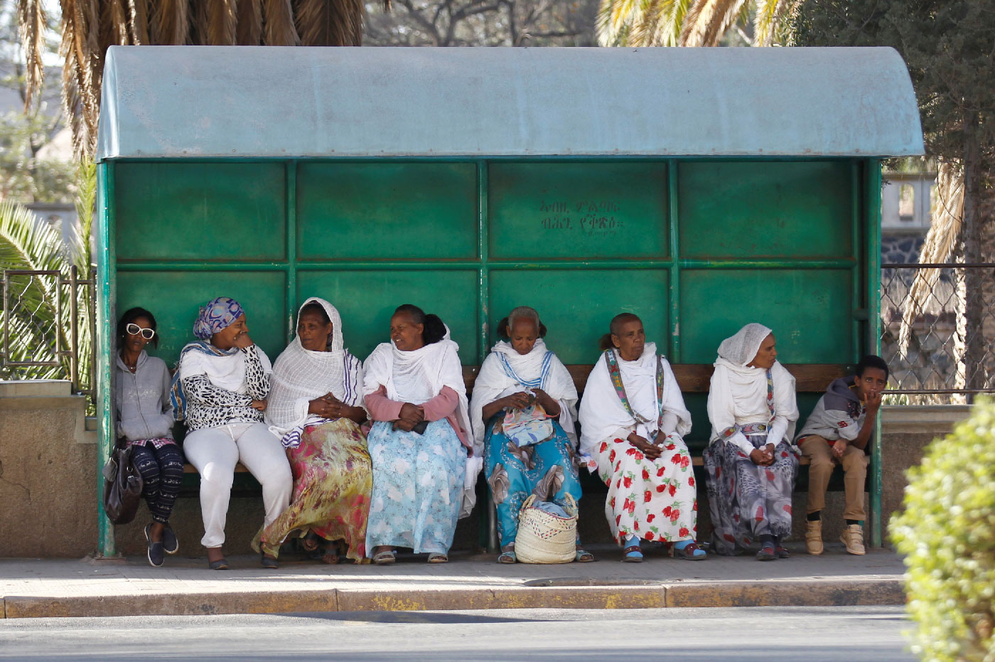 Passengers wait for the bus at a stop along a street in Asmara, Eritrea.