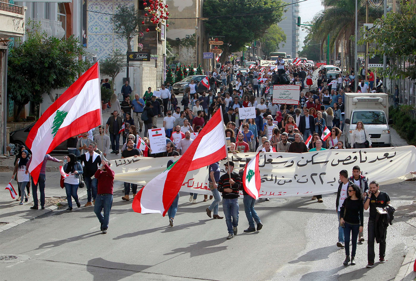 Protesters hold banners and Lebanese flags in Beirut