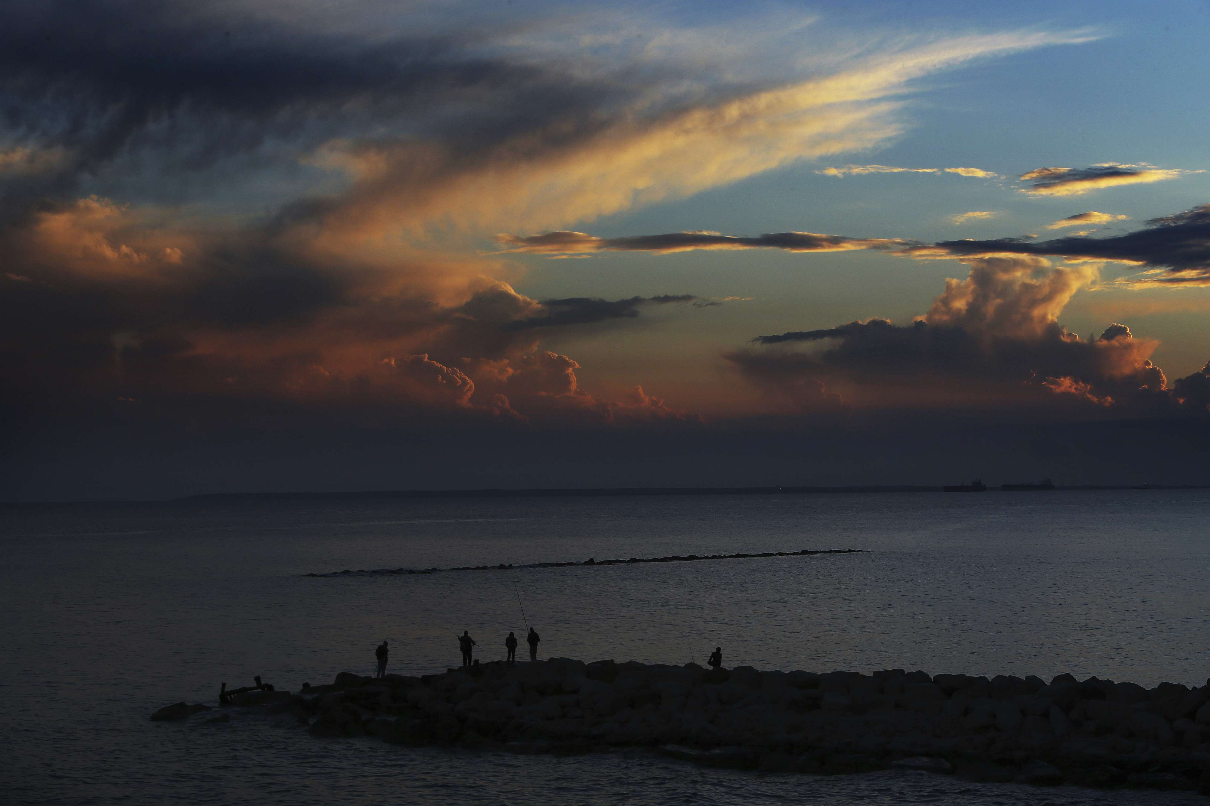 Men fishing with their fishing rods at the sea during a sunset in the southern port city of Limassol, Cyprus, Friday, Feb. 23, 2018.