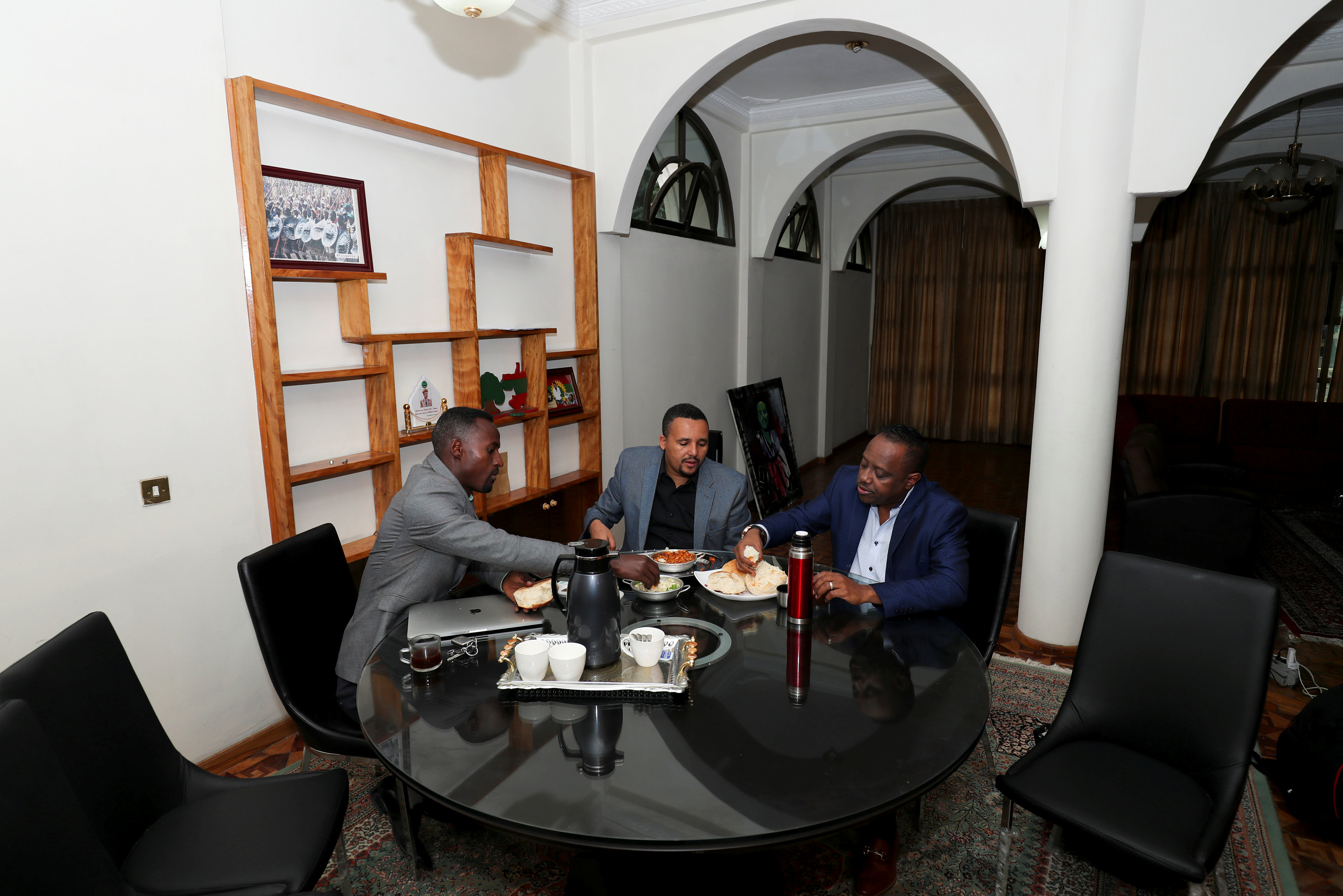 Jawar Mohammed (C), 32, eats breakfast with his colleagues at his house in Addis Ababa.