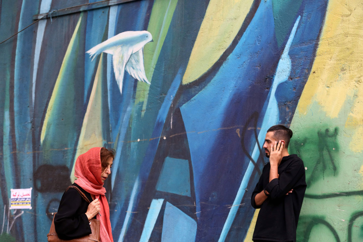 Iranians walk past colourful walls in the capital Tehran.