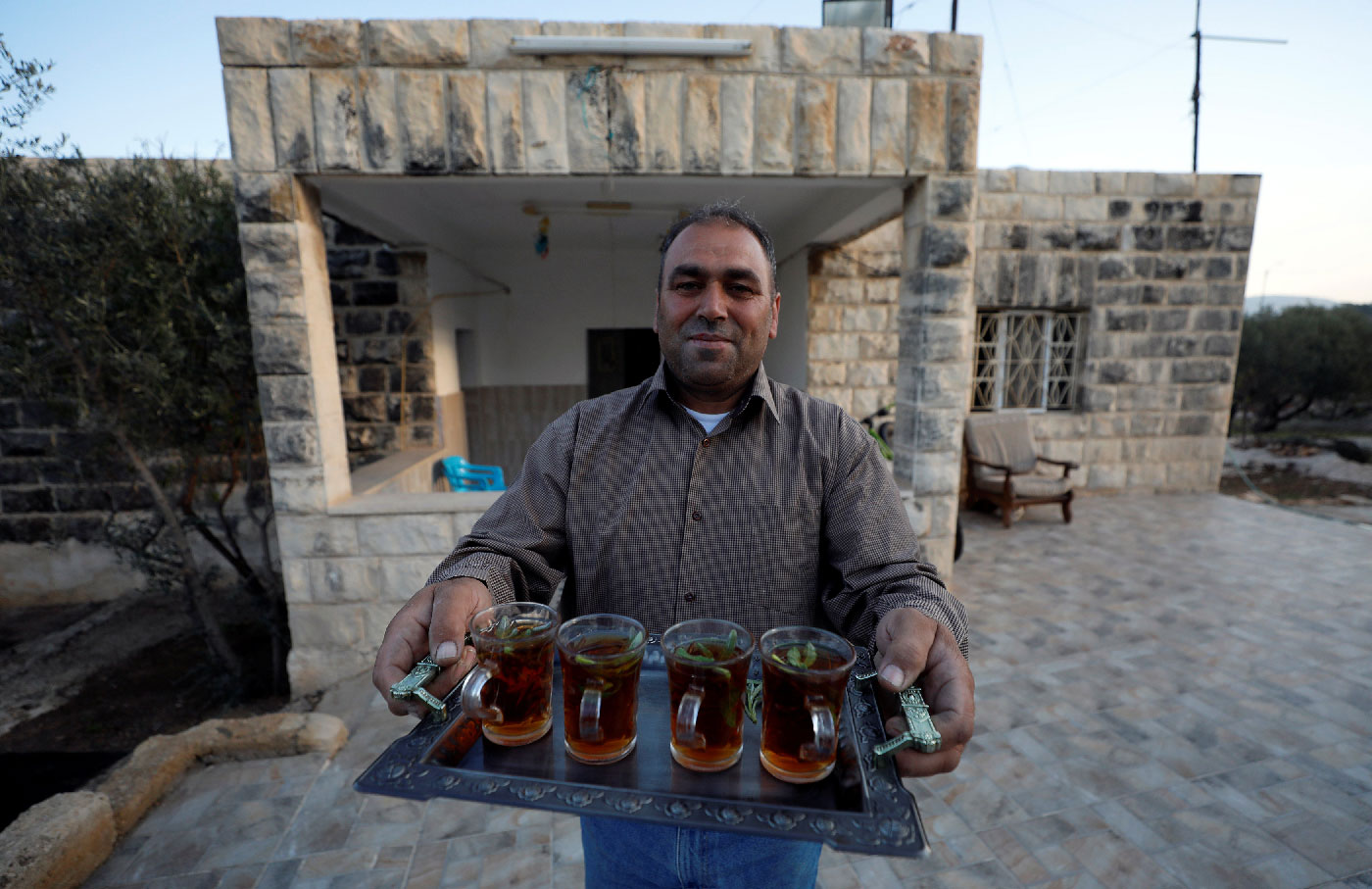 The uncle of Rashida Tlaib, the first Palestinian-American woman to be elected to the U.S. Congress, offers tea after her victory, in Beit Ur Al-Fauqa, in the occupied West Bank November 7, 2018.