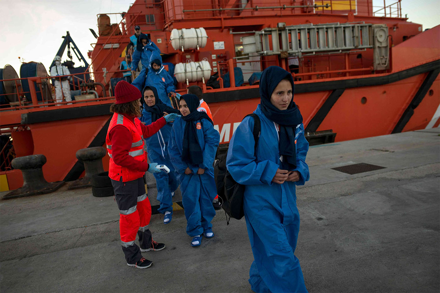 Migrants are transferred upon their arrival aboard a coast guard boat at Algeciras' harbour