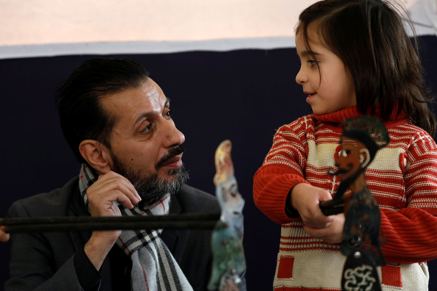 Shadi al-Hallaq, a puppeteer, is seen next to a disabled child during a performance in Damascus, Syria December 3, 2018.
