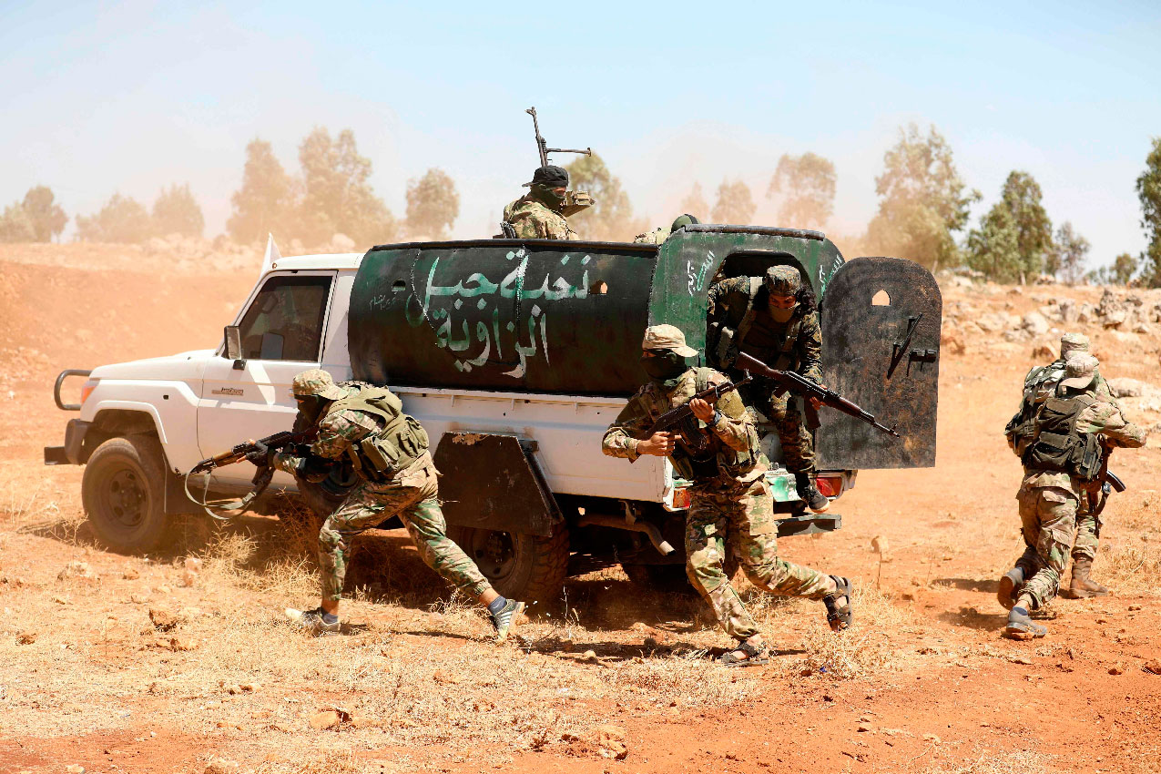 In this file photo taken on August 14, 2018 Syrian fighters attend a mock battle in anticipation of an attack by the regime on Idlib province and the surrounding countryside, during a graduation of new Hayat Tahrir al-Sham (HTS) members at a camp in the countryside of the northern Idlib province.