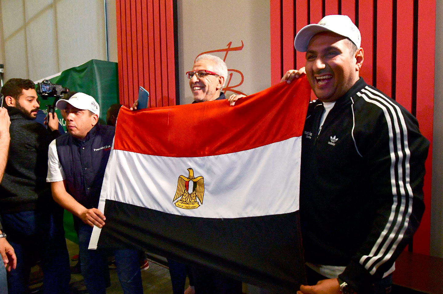 Egyptian representatives pose with their national flag as they celebrate the Confederation of African Football (CAF) executive committee's decision to choose Egypt to host the 2019 Africa Cup of Nations between June 15 and July 13, in an Hotel in Dakar on January 8, 2019.