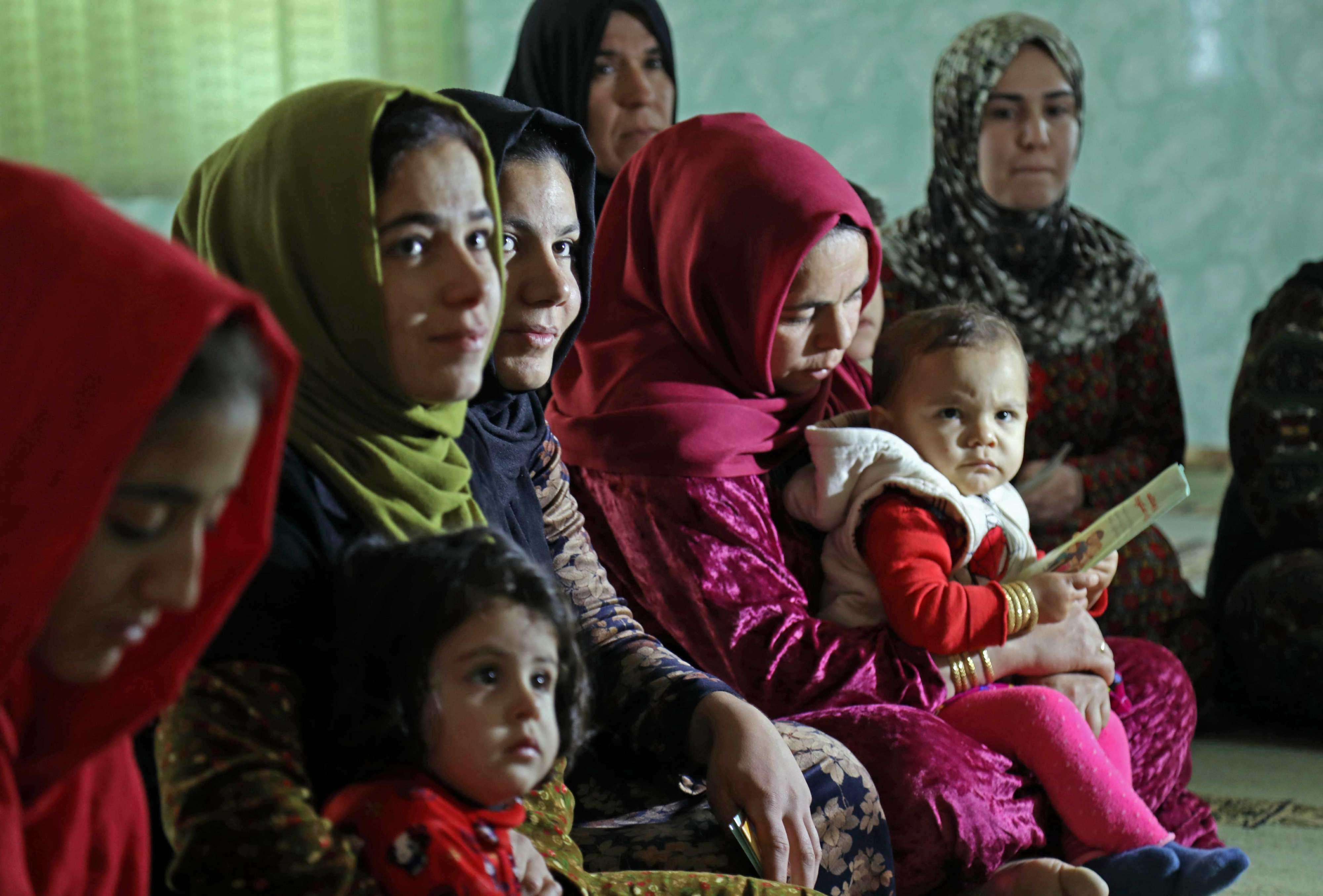 Women and young girls listen to Rasul (not pictured) an Iraqi Kurdish activist with the non-profit organisation WADI, as she peaks about the harms of genital mutilation in Sharboty Saghira, a small village east of regional capital Arbil, on December 3, 2018.