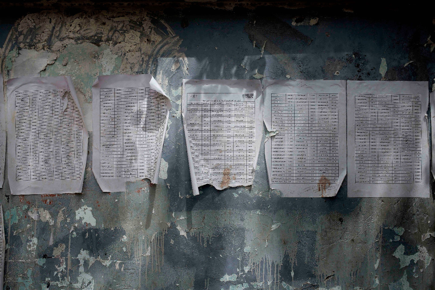 A worn-out list of registered names for aid by Relief International, part of the World Food Program, is posted in Aden, Yemen on July 23, 2018.
