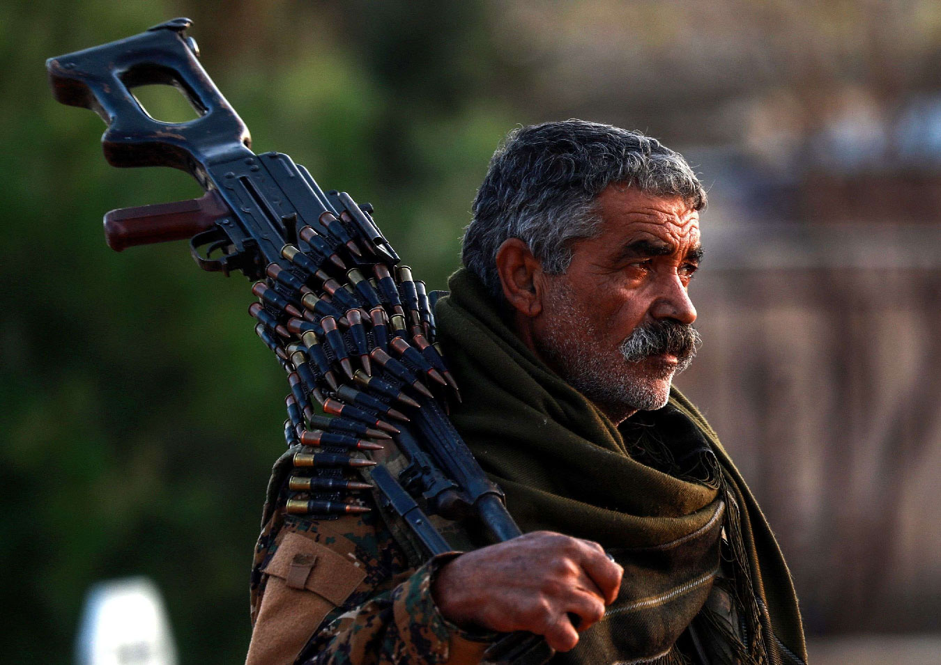 A Syrian Democratic Forces (SDF) fighter holds a machine gun on his shoulder as he attends the funeral of a slain People's Protection Units (YPG) commander in the northeastern city of Qamishli on December 6, 2018.