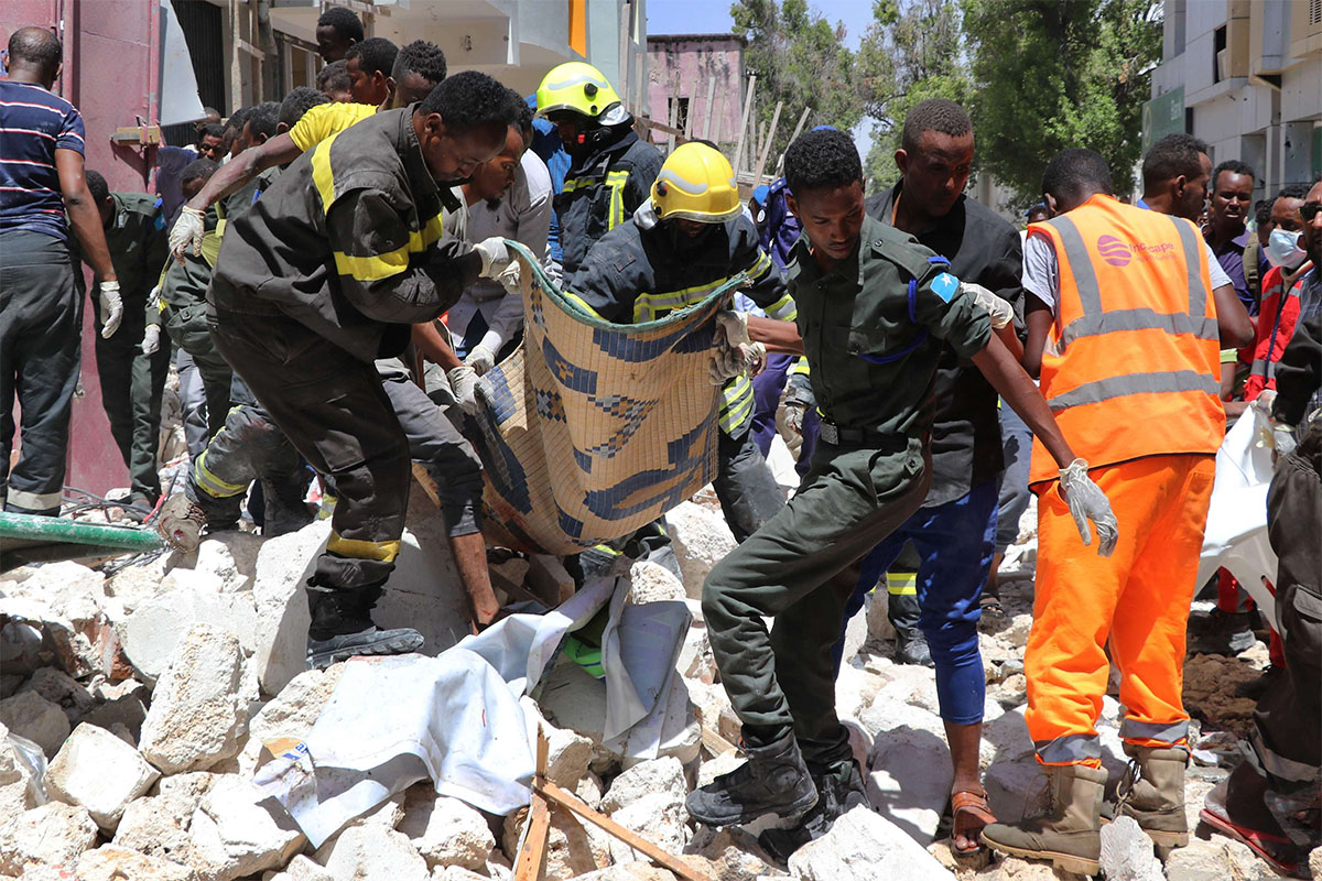 Emergency rescue staff carry the body of a victim over rubble at the scene of the car-bomb attack
