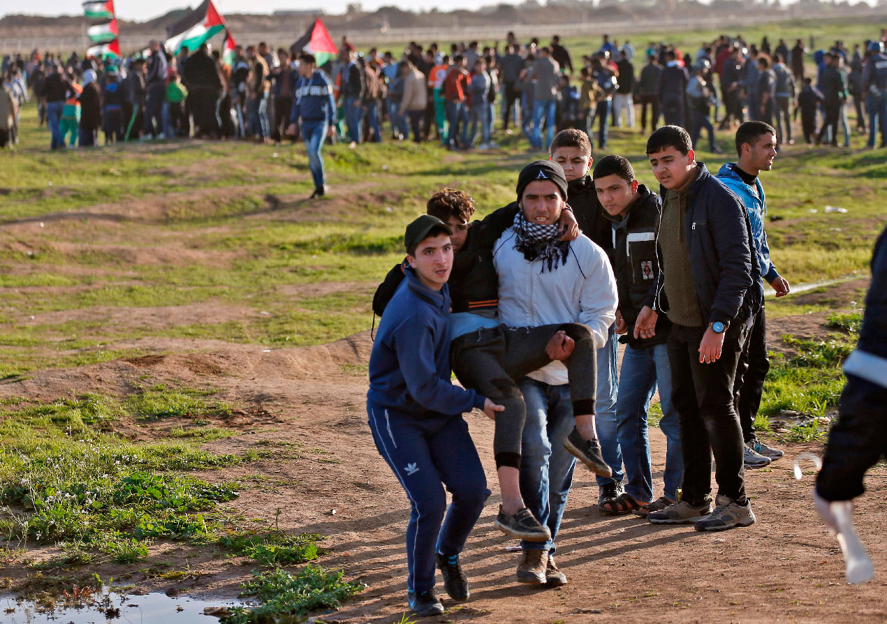 Palestinian demonstrators evacuate a wounded comrade during a demonstration near the fence east of Gaza City, on February 8, 2019.
