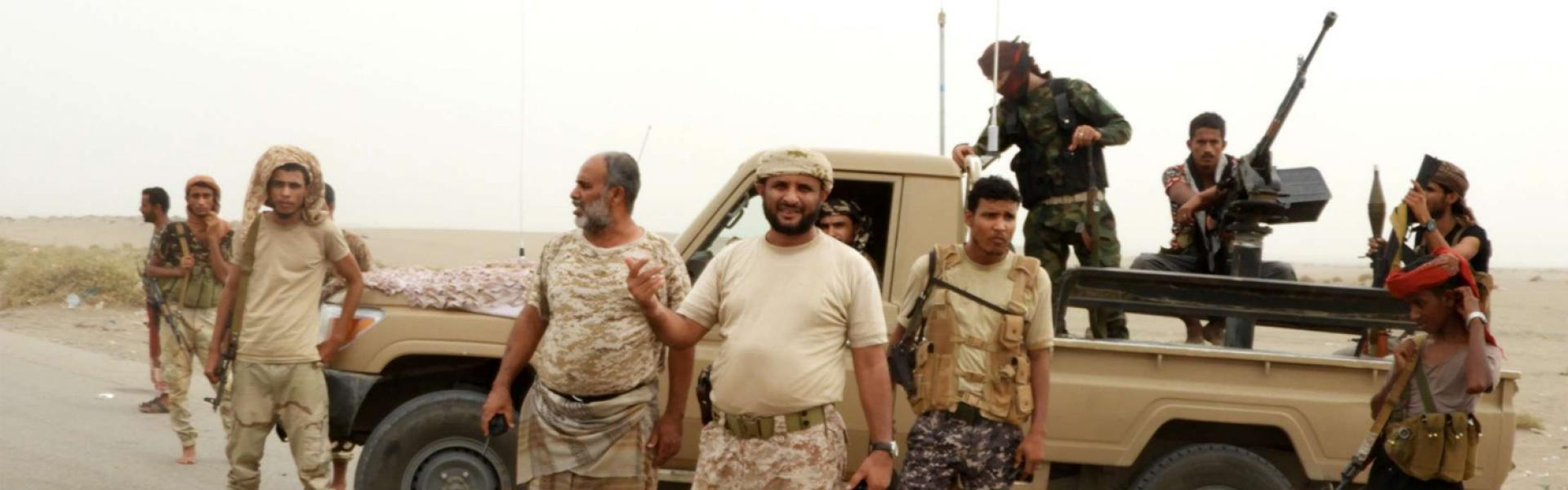 Yemeni pro-government forces stand next to a pickup truck carrying anti-aircraft guns outside Hodeidah