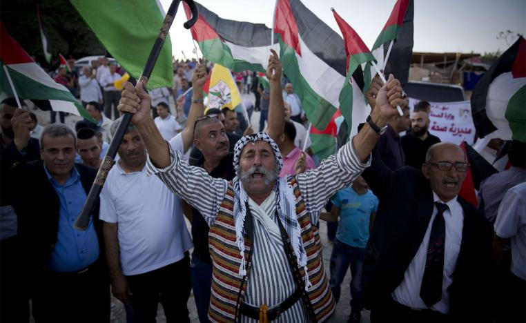 Palestinians protesters fly national flags and chant anti Israel slogans in the West Bank hamlet of Khan al-Ahmar