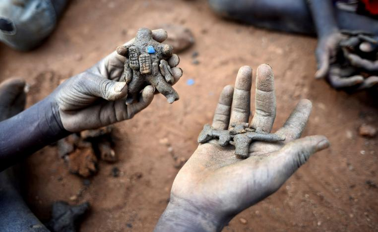Displaced child holds clay model toys of a peacekeeper and a rifle in Juba, South Sudan.