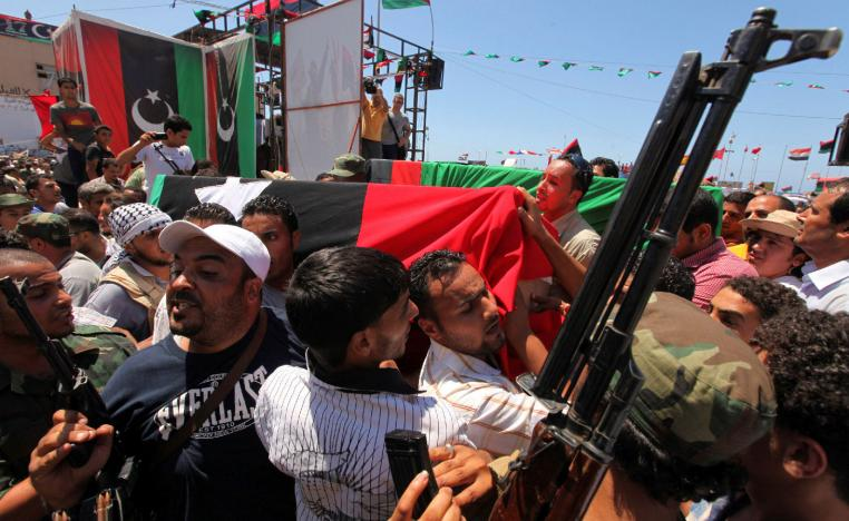 People attend the burial of Libyan rebel military commander Abdel Fattah Younes in Benghazi July 29, 2011.