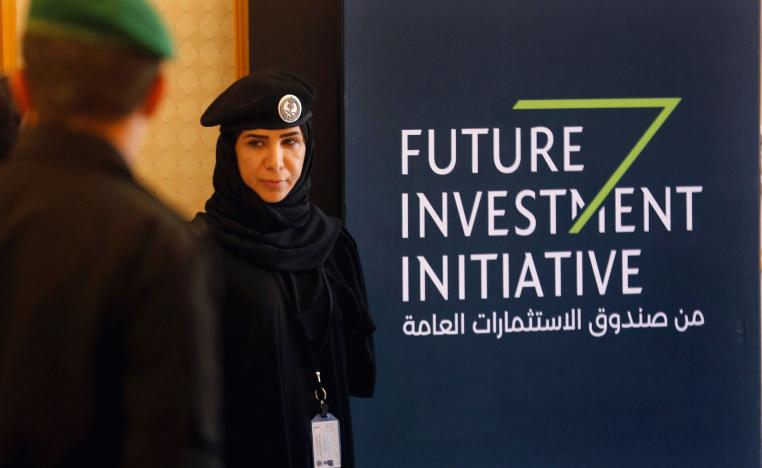 A Saudi policewoman stands near a banner for the Future Investment Initiative conference, in Riyadh, Saudi Arabia