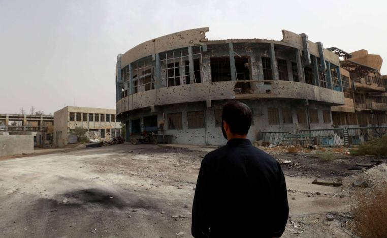 A member of the first response team tours the courtyard of the National Hospital building in the northern Syria city of Raqa