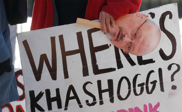 An activist holds a sign and image of missing Saudi journalist Jamal Khashoggi during a demonstration in Washington