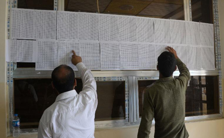 Iraqis check lists of names at the Nineveh governorate building in Mosul.