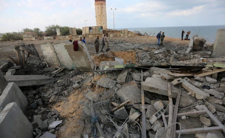 Palestinian men inspect the damage at a site targeted by an Israeli air strike.