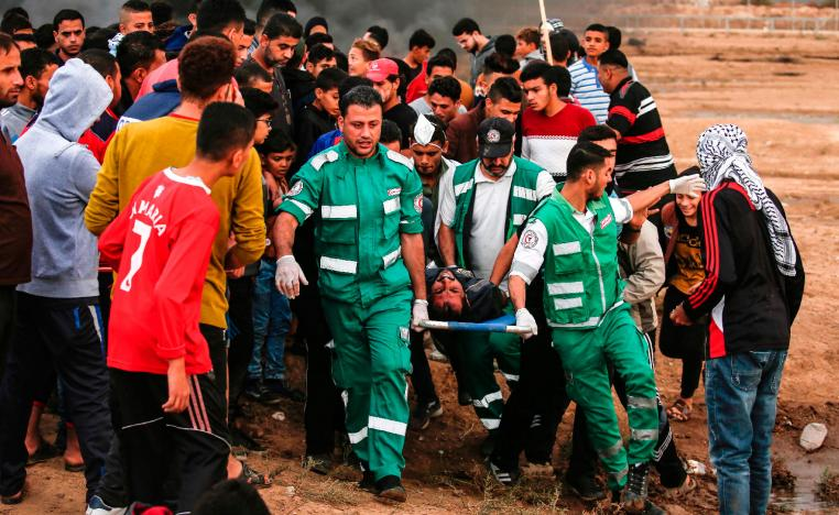 Palestinian paramedics carry away on a stretcher a protester who was injured during protests.