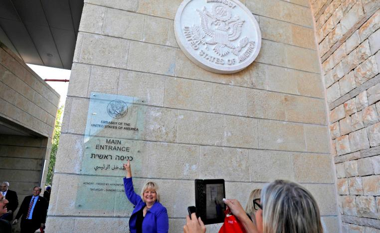 A woman poses for a picture next to an inauguration plaque during the opening of the US embassy in occupied Jerusalem.