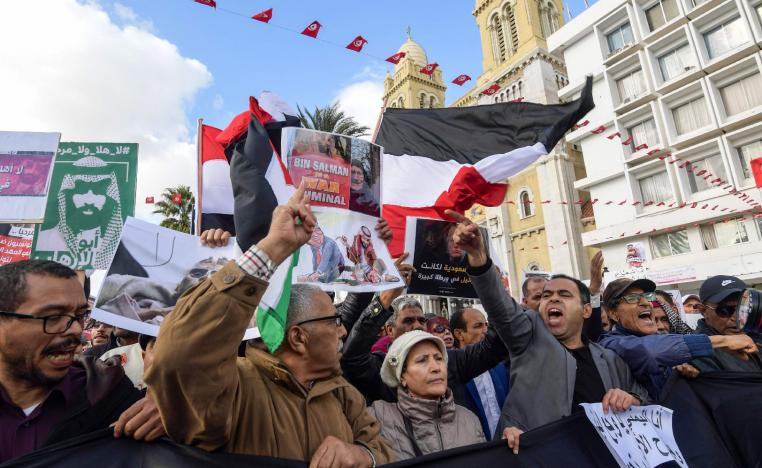 Tunisians shout slogans and hold up signs as they protest against the expected visit of the Saudi Crown Prince.