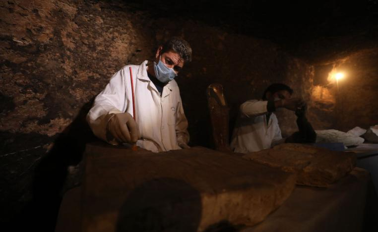 gyptian archaeologists work inside a tomb in the Saqqara necropolis.