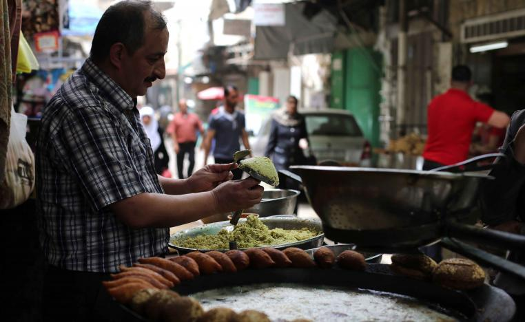 More than what's on a plate. A Palestinian man makes falafel, a traditional dish consisting of fried chickpeas, on a street in Nablus
