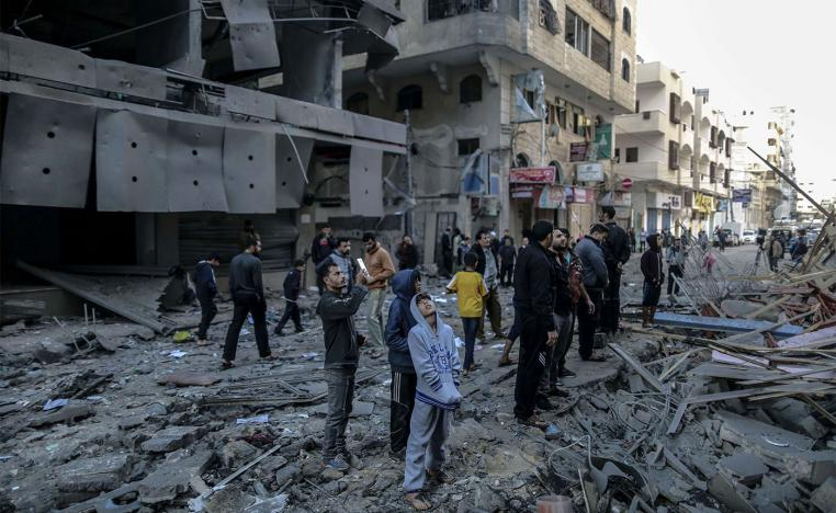Palestinians inspect the damage of a destroyed residential building in Gaza after hitting by Israeli air strikes