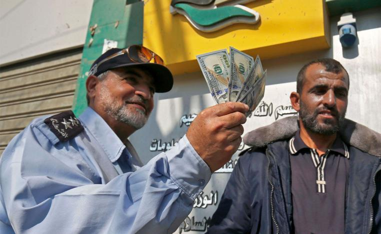 A Palestinian man shows his money after receiving his salary in Rafah in the southern Gaza Strip