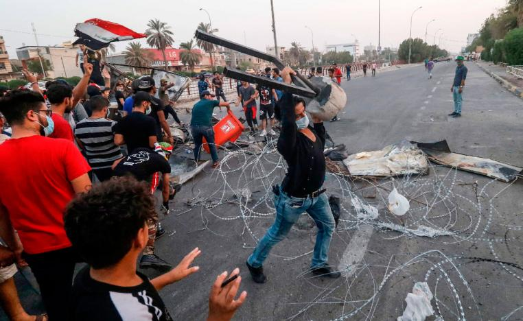 In this file photo taken on September 2, 2018, Iraqi protesters gather trash cans and scrap with barbed wire as they erect a make-shift barricade during clashes with security forces following a demonstration against corruption and lack of basic services outside the local government headquarters in the southern city of Basra.