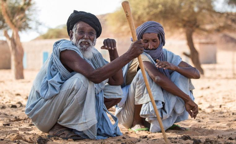 Men sit on the ground in Ouad Initi, eastern Mauritania, on November 21, 2018.
