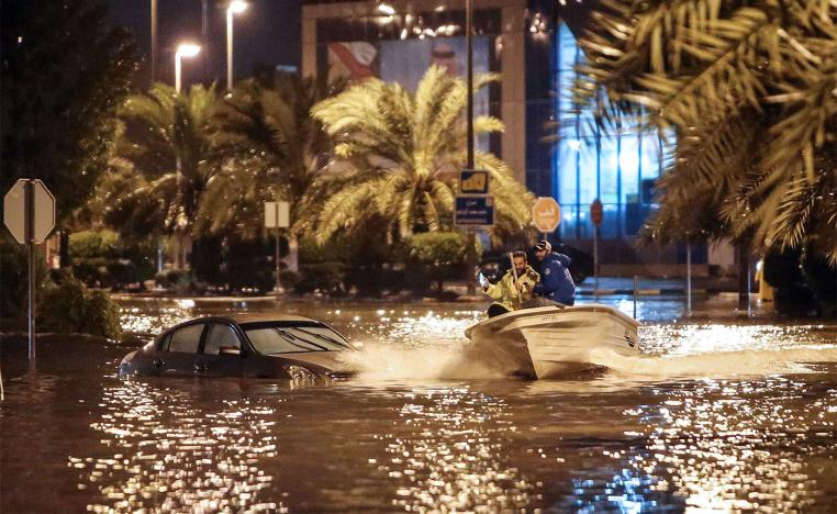 People are using a boat on the flooded main road of the Daeya area of Kuwait city