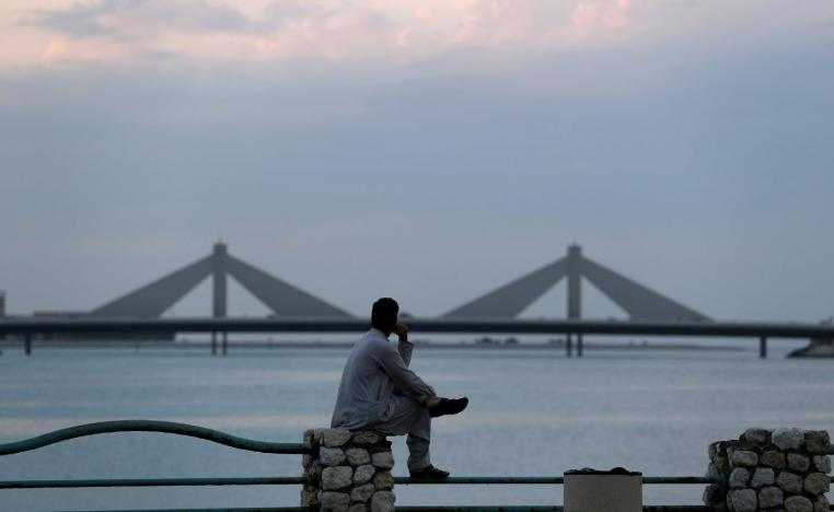 A man sits and looks towards the Sheikh Isa Causeway, linking Diplomatic Area to Muharraq, during the early evening hours in Manama, Bahrain, November 11, 2018.