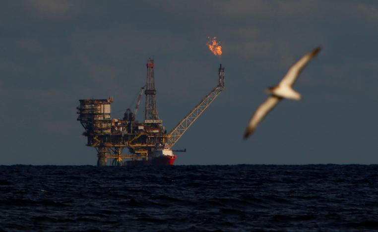 A seagull flies in front of an oil platform in the Bouri Oilfield some 70 nautical miles north of the coast of Libya, October 5, 2017.