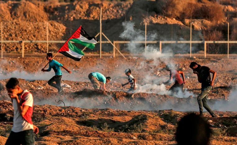 Palestinian protesters react to tear gas fired by Israeli forces during clashes east of Gaza City near the Israeli border on November 2, 2018.