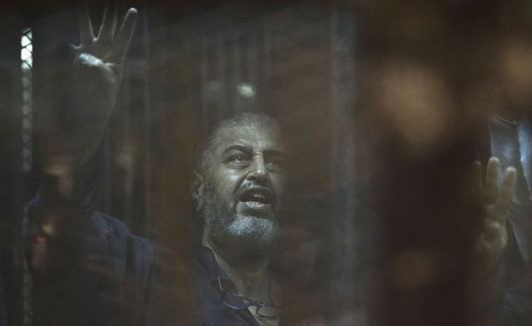 Egyptian Muslim Brotherhood financier Khairat al-Shater gestures from behind the defendant's cage as he attends his trial in Cairo on June 16, 2015.