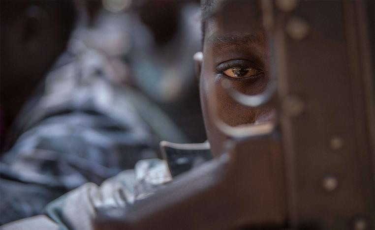 A released child soldier last February looks through a rifle trigger guard during a release ceremony for child soldiers in Yambio, South Sudan