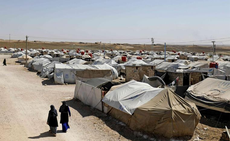 Women walk at a camp for Islamic State (IS) group-affiliated people in the northern Syrian village of Malikiya