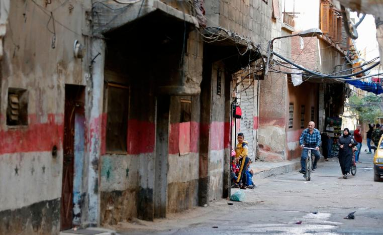 People walk in a street in Tadamun neighbourhood.