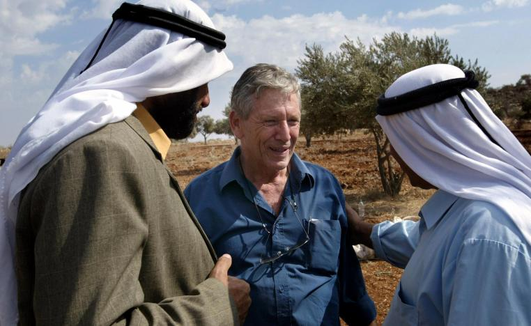 In this file photo taken on October 30, 2002 Israeli writer Amos Oz (C) talks with Palestinian men after picking olives in the West Bank village of Aqraba, south of Nablus.