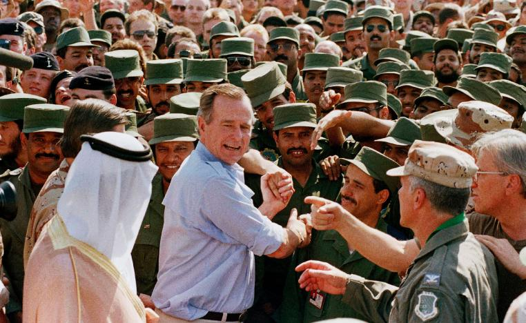 A file photo shows former US President George H.W. Bush being greeted by Saudi troops and others as he arrives in Dhahran, Saudi Arabia, in 1990.