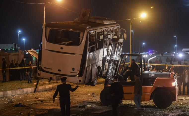 A damaged tourist bus is being removed after it was struck by a roadside bomb near the Pyramids of Giza at the district of al-Maryutia, on December 28, 2018.
