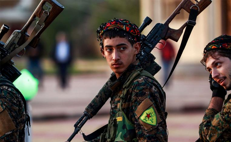 Syrian Democratic Forces fighters hold a sniper rifle