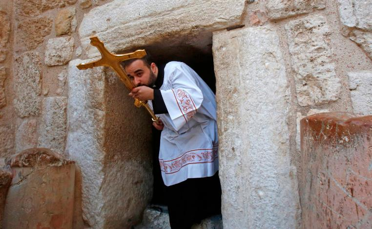 A Latin clergy carries a cross at the Church of the Nativity in the West Bank city of Bethlehem on December 24, 2018.