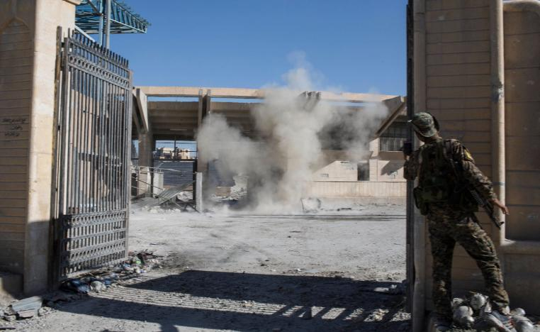A member of the U.S.-backed Syrian Democratic Forces SDF throws a bomb to check for more explosives as they clear the stadium that was the site of Islamic State fighters' last stand in the city of Raqqa, Syria.